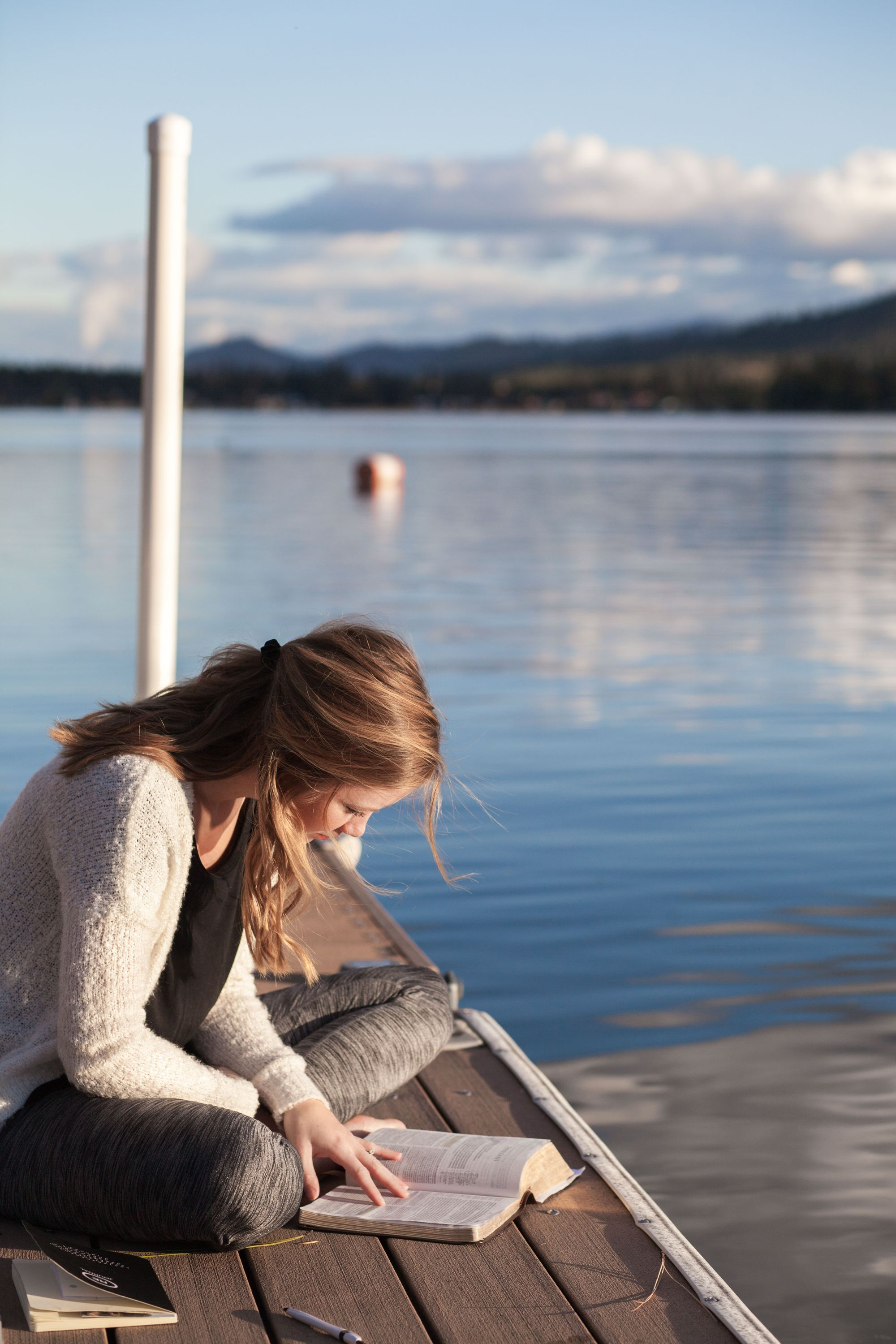 girl reading book on dock